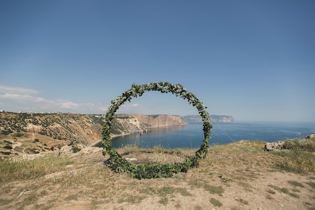 Wedding arch in the form of a ring on a cliff on the background of the ocean