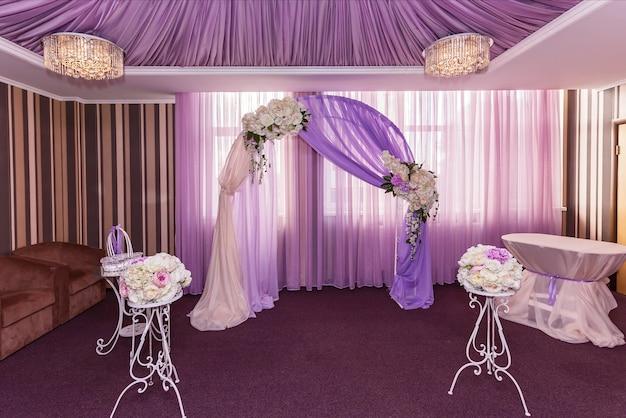 バラのあるホールの結婚式のアーチ。結婚式のアーチ。