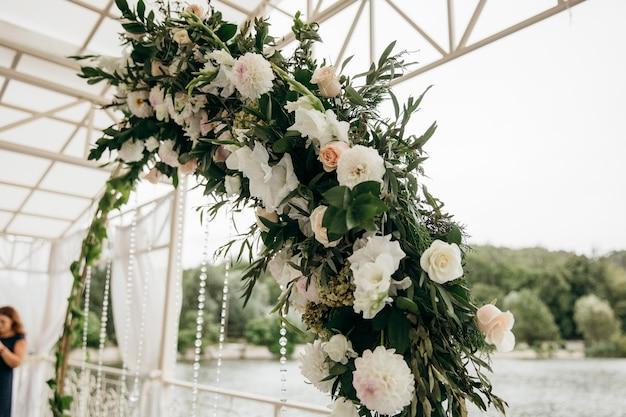 Свадебная арка украшена красивыми букетами роз.