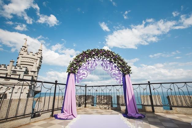 Свадебная арка фиолетового цвета на фоне моря.