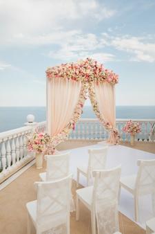 海の背景に花模様の結婚式のアーチ桃色