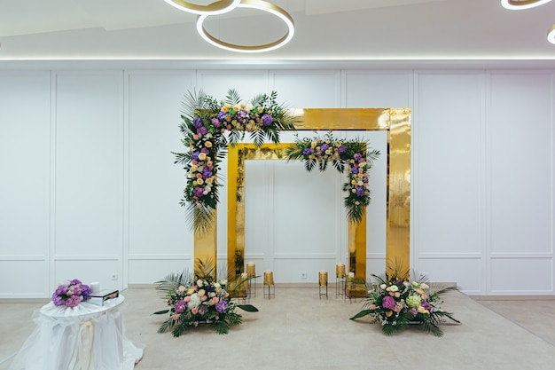 The wedding arch in the restaurant is decorated with fresh flowers and gold plates