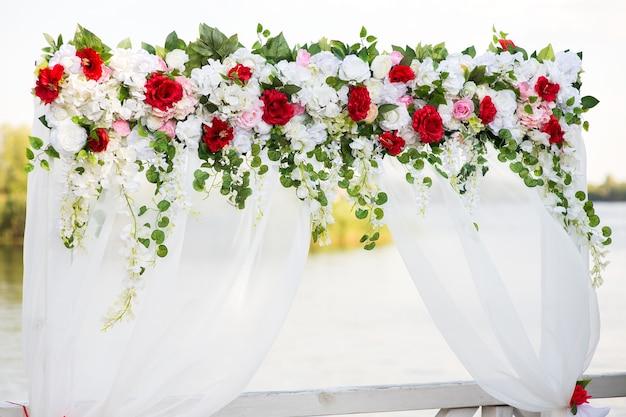 Свадебная арка с искусственными цветами и белой тканью
