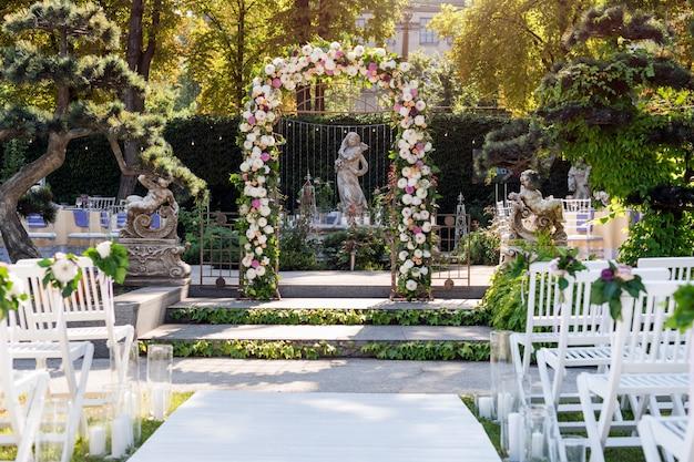Свадебная арка с цветами на открытом воздухе. свадебная церемония в саду со скульптурами и фонтаном.