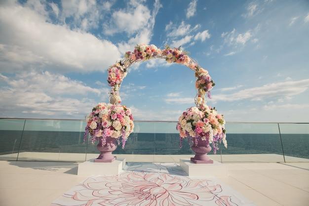 海の背景に新鮮な花で結婚式のアーチ。生花と花瓶。
