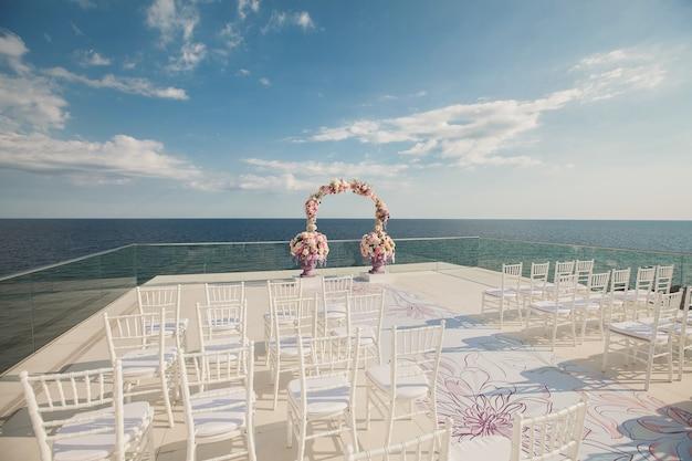 海を背景に新鮮な花と結婚式のアーチ。生花の花瓶。