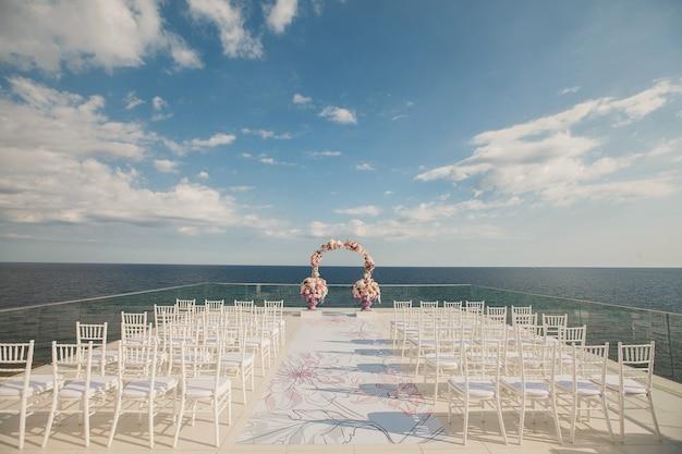 海の背景に新鮮な花で結婚式のアーチ