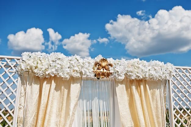 白い花と黄金の飾りの結婚式のアーチ
