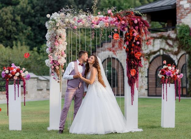 뒤뜰에 결혼식 아치 밑의 통로 및 결혼식 전에 야외에서 행복한 웨딩 커플