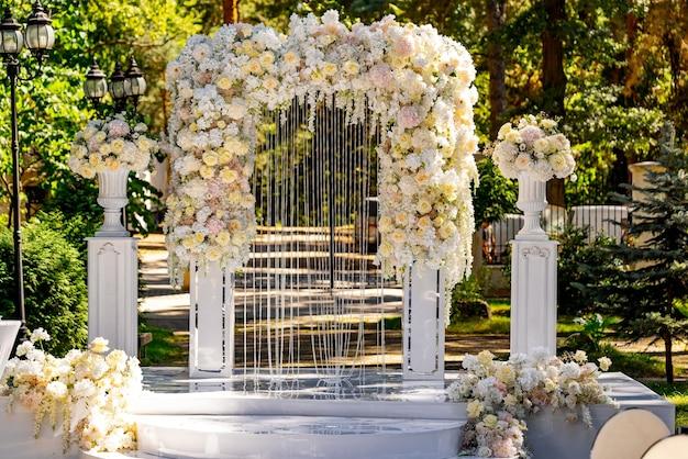 결혼식을 위해 공원에 꽃이 놓인 결혼식 아치 밑의 통로. 축하를 위한 부드러운 아치.
