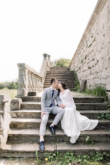 Wedding, asian groom and bride holding hands, while sitting on the ancient stone stairs, next to old castle.