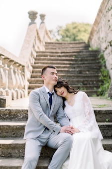 Wedding, asian groom and bride holding hands, while sitting on the ancient stone stairs, next to old castle