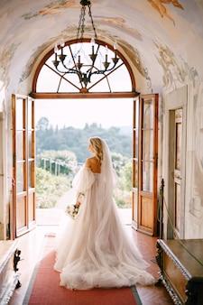 イタリア、トスカーナの古いワイナリーヴィラでの結婚式。花嫁は別荘の内部に立ち、庭を見下ろします。
