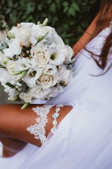Wedding attributes bandage on the leg, bouquet, dress