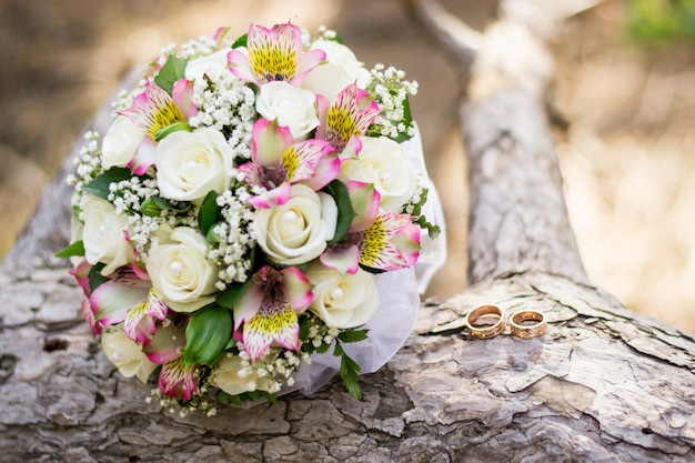 Wedding background bouquet and rings on wood.