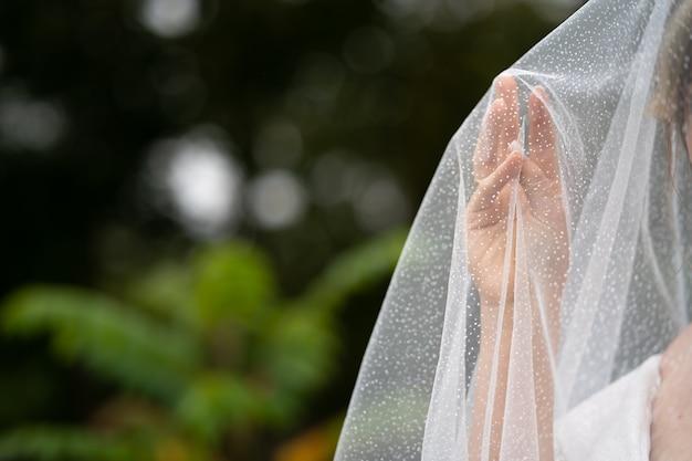 結婚式の背景、ベールの下の花嫁の手。
