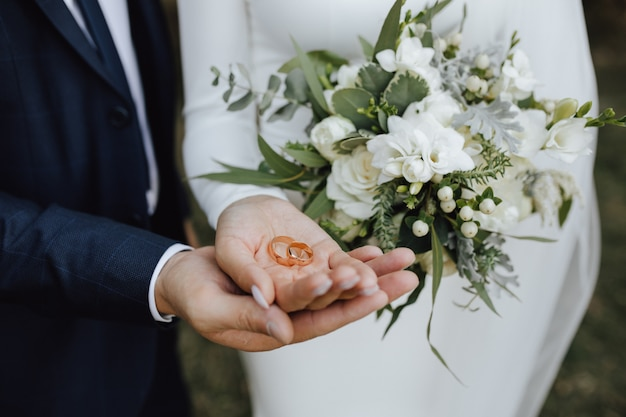 Wedding bands in the hands of bride and groom and with beautiful wedding bouquet made of greenery and white flowers
