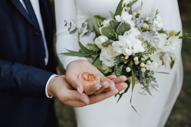 Обручальные кольца в руках жениха и невесты и с красивым свадебным букетом из зелени и белых цветов
