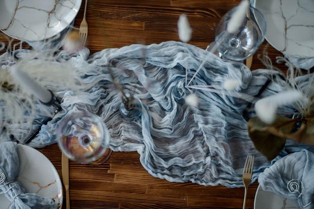 結婚式の宴会。明るい色のお祭りの装飾。カトラリー、キャンドル、ドライフラワー、リネンスカイブルーランナーを添えて木製のテーブル。上面図