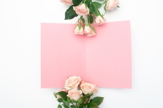 Wedding or birthday mock up scene. blank open sheet of paper with place for text for greeting card. bouquet of pink roses.
