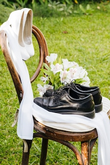 Wedding black shoes and white high heels with flower bouquet on wooden chair in the garden