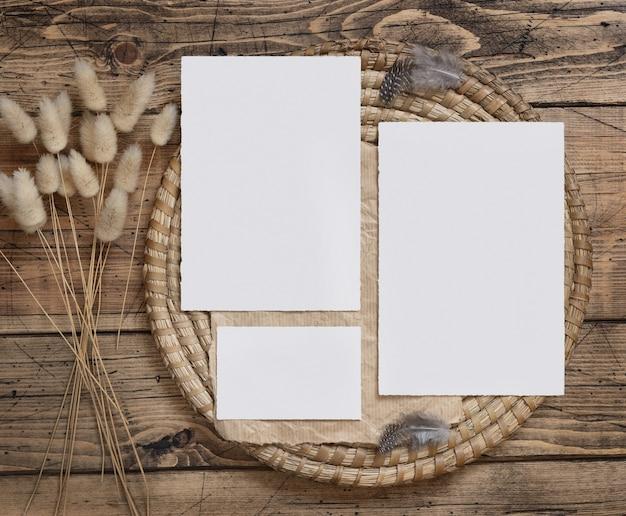 Свадебные пустые карточки, лежащие на коричневом деревянном столе с засушенными цветами и перьями вокруг вида сверху. женский макет в стиле бохо с плоской планировкой