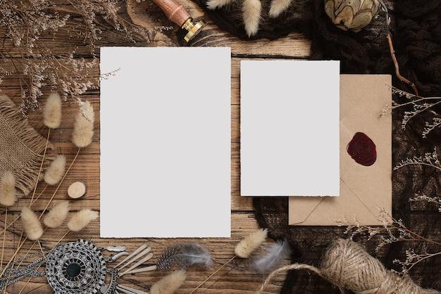 Свадебные пустые карты, лежащие на деревянном столе с богемным декором вокруг