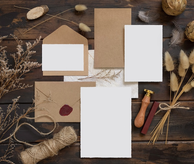 Wedding blank cards laying on a wooden table with bohemian decoration around