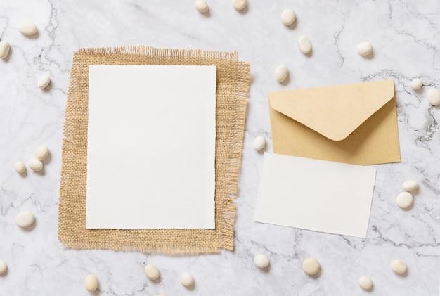 Свадебные пустые открытки с конвертом, лежащим на мраморном столе, украшенном маленькими белыми камнями. макет карты