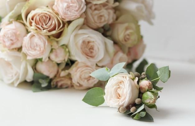 Свадебный букет и бутоньерка из белых цветов на белом фоне