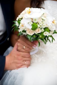 반지와 손과 웨딩 부케