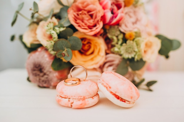 Wedding bouquet in autumn colors, wedding rings and macaroons on a white table.