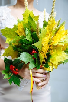 Wedding bouquet of autumn leaves and berries in the hands of the bride.