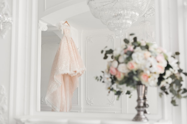 Wedding bouquet on the background of a luxurious wedding dress on a hanger