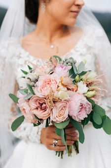 Wedding bouquet. beautiful flowers in bride's hands in a white dress. eucalyptus and roses