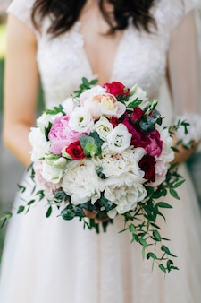 Wedding bouquet. beautiful flowers in bride's hands in a white dress.