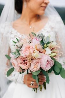 Свадебный букет. красивые цветы в руках невесты в белом платье. эвкалипт и розы