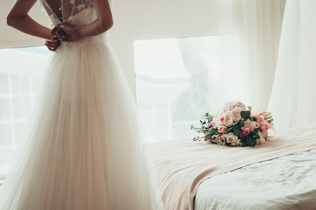 A wedding bouquet on a bed, with blurred bride buttoning her dress, back view
