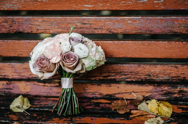 The wedding bouquet of the bride is on a bench with yellow autumn leaves in the park