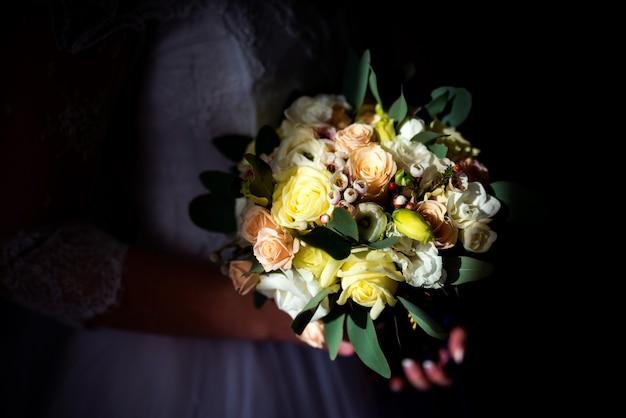Wedding bouquet in bride's hands over dark