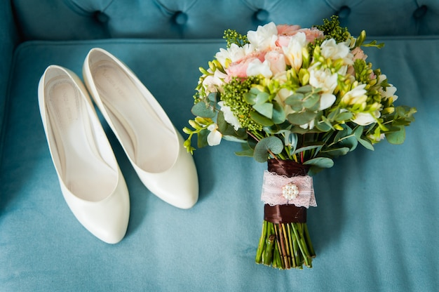 Wedding bouquet and bridesmaid shoes on blue mat