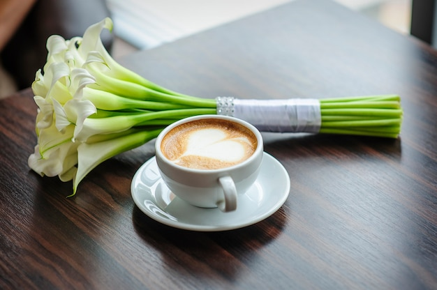 Wedding bouquet of calla lilies on a table with a cup of coffee.