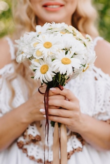 Wedding bouquet of daisies in the hands of the bride on the background of a white dress