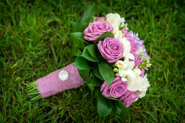 Wedding bouquet of flowers lying on green grass