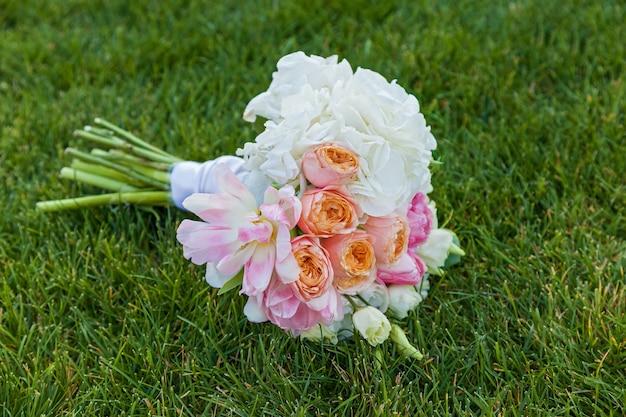 緑の芝生の上の花嫁のためのウェディングブーケ