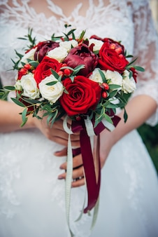 Wedding bouquet of fresh flowers in bride's hands, cropped image, close-up. young bride holding a bouquet of white and red roses.