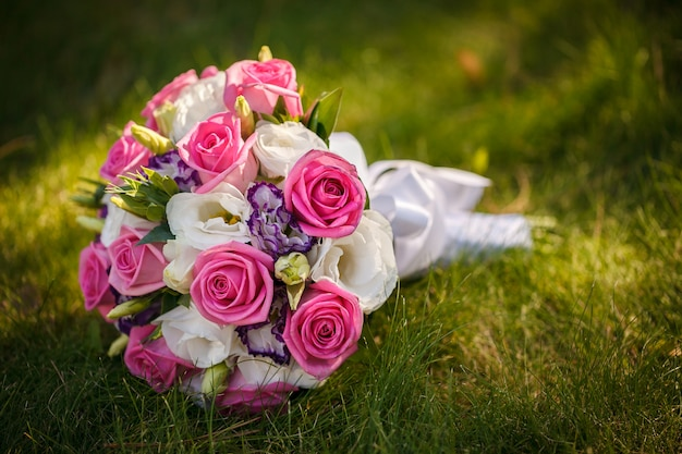 Wedding bouquet from roses on a green grass