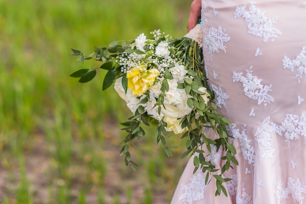 Wedding bouquet in hands of the bride on background of the dress