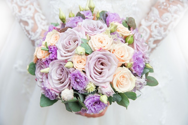 Wedding bouquet in the hands of the bride on the background of a white dress
