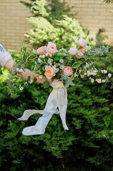 Wedding bouquet in the hands of the bride, david austin rose, green background